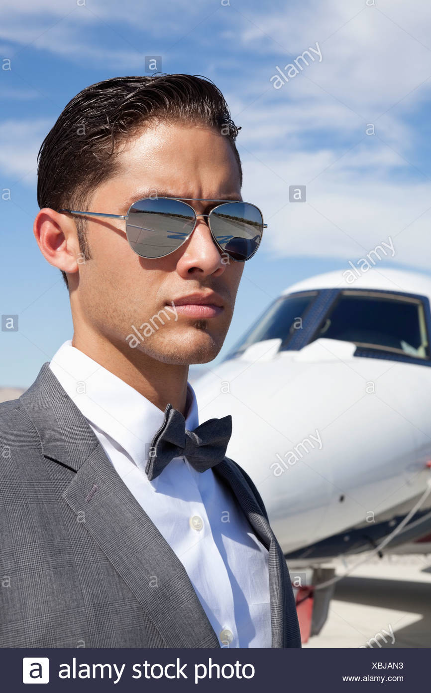 Handsome young men wearing sunglasses private plane in background - Stock Image