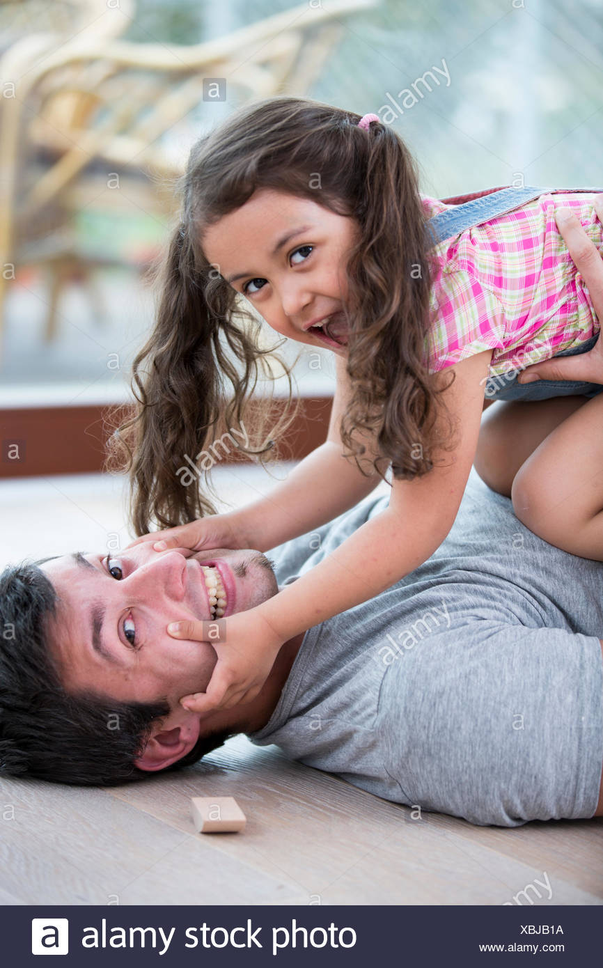 Mischievous daughter on top of father at home - Stock Image