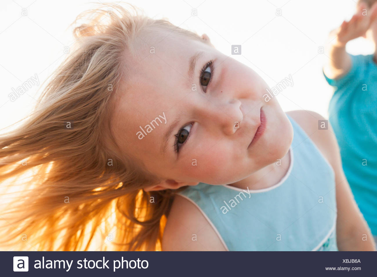 Portrait of girl, head cocked, looking at camera smiling - Stock Image