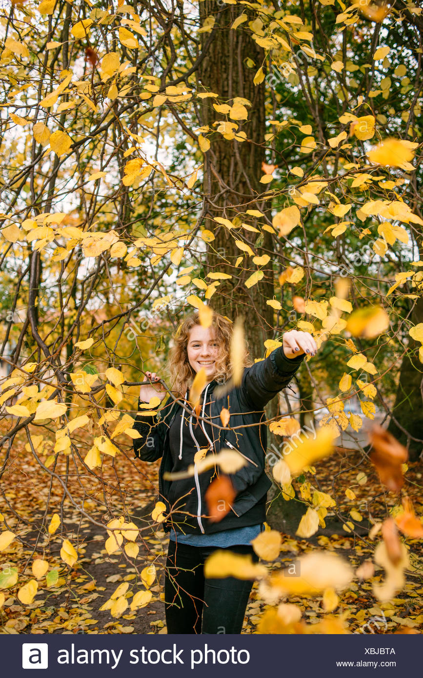 Leaves falling on girl (16-17) in park - Stock Image