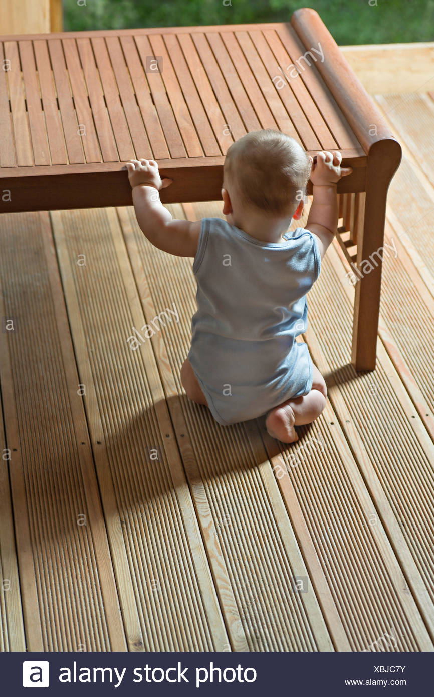rear view of baby sitting in front of table - Stock Image