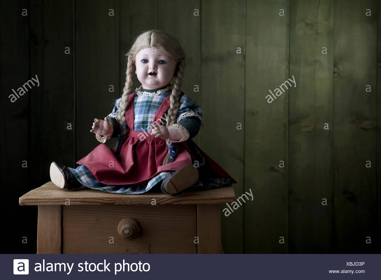 Antique doll sitting on a small chest of drawers - Stock Image