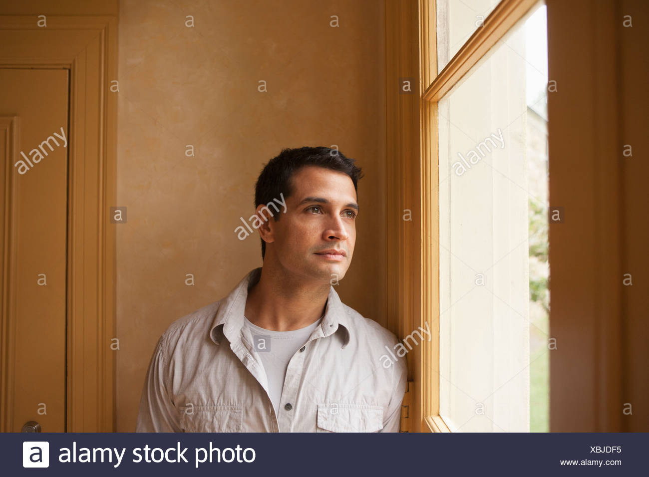 USA, New Jersey, Portrait of man looking out window - Stock Image