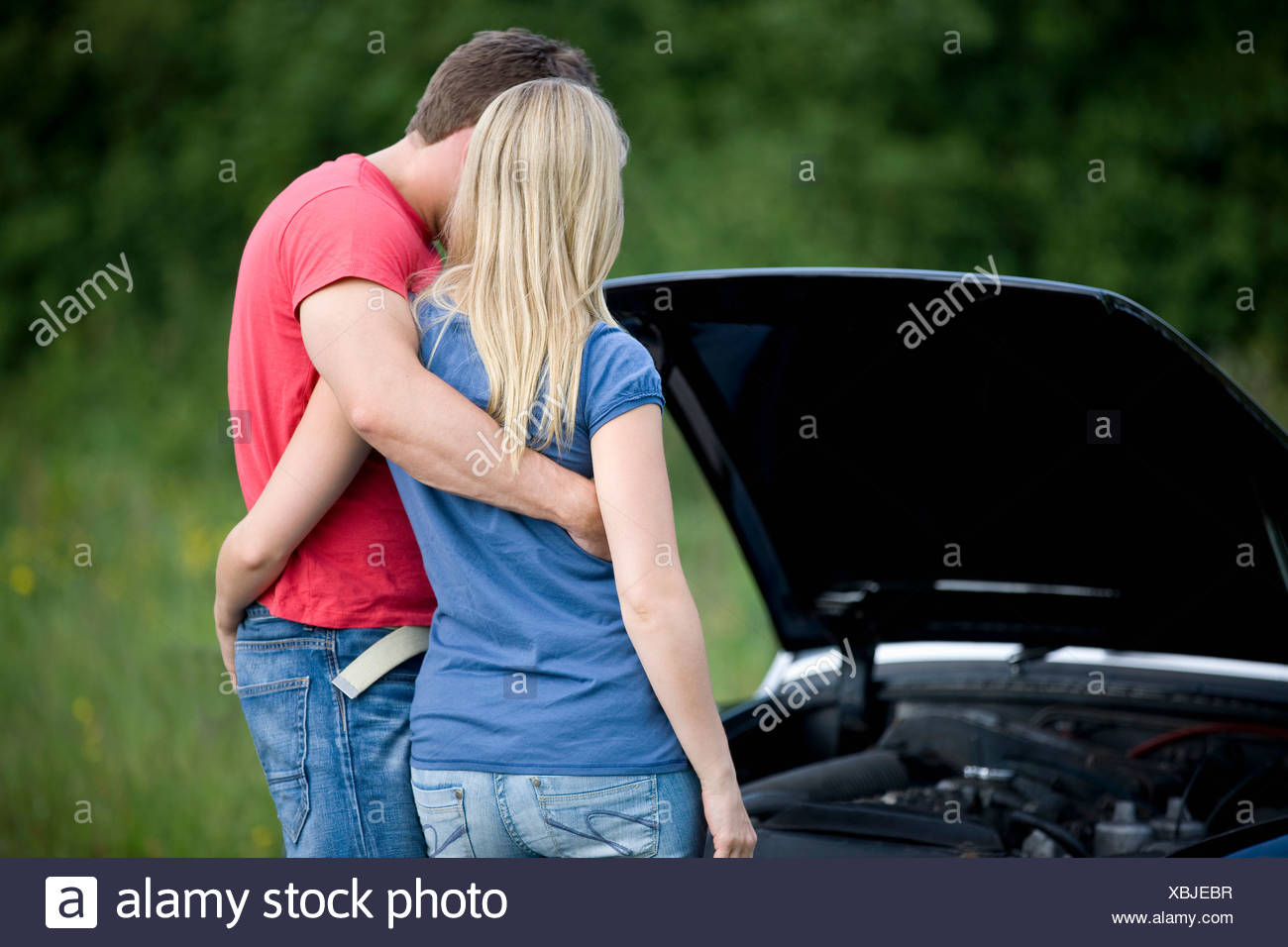 A young couple standing next to their broken down sports car, looking at the cars engine - Stock Image