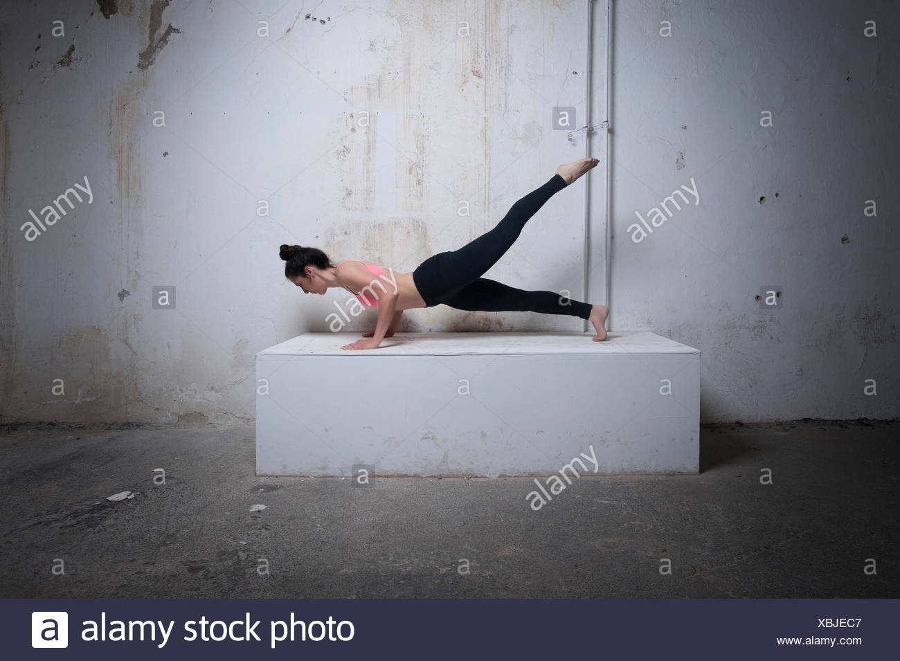 Mid adult woman practicing plank pose on concrete block, Munich, Bavaria, Germany - Stock Image