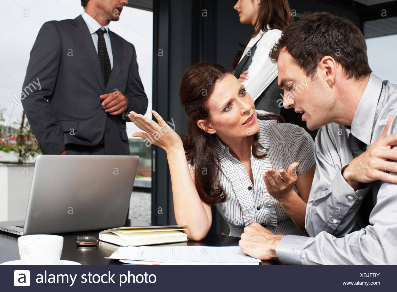 Business woman speaking to a younger man - Stock Image