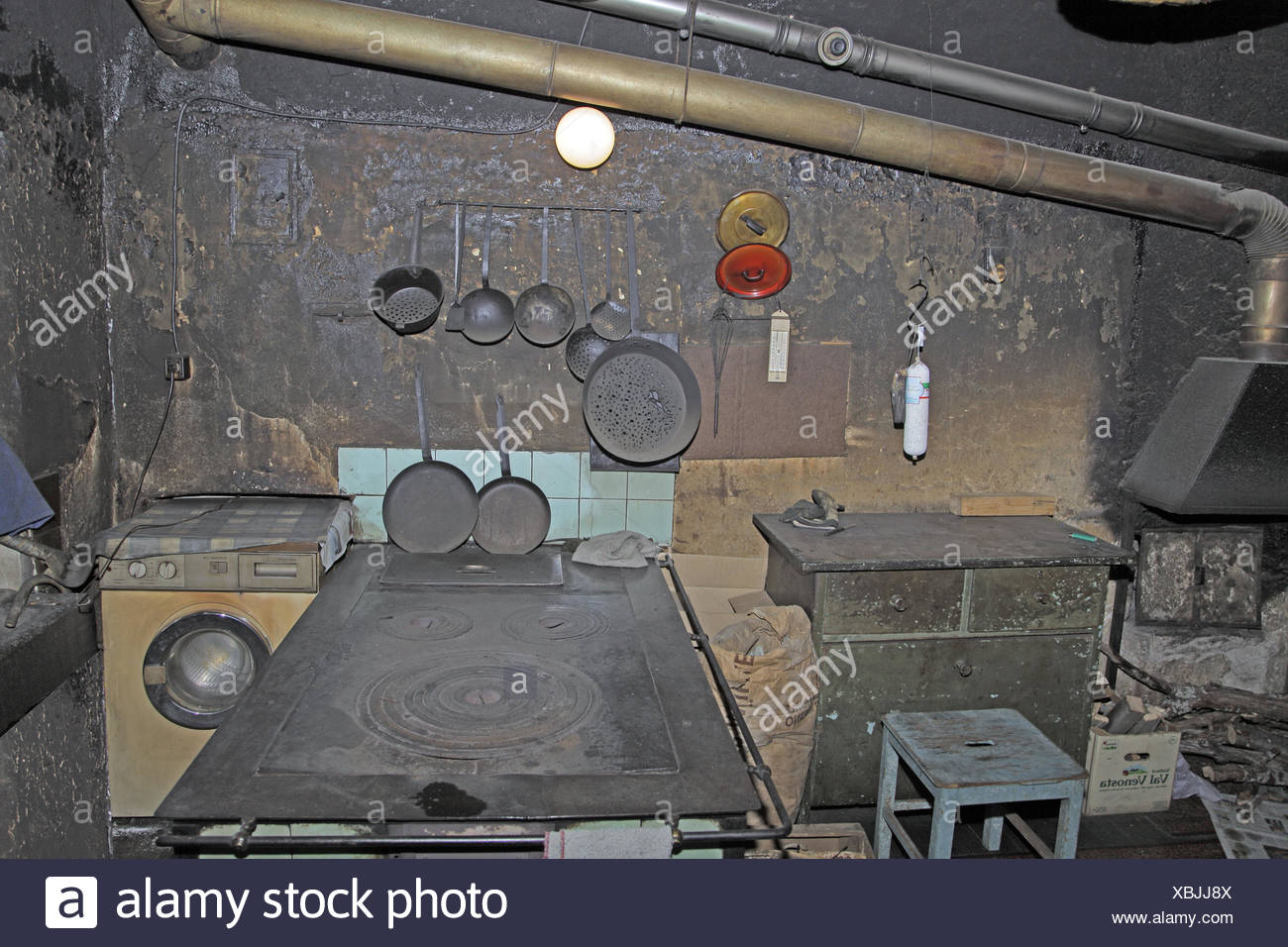 Smoke cuisine, old, Italy, South Tyrol, Ultental, Ulten, cuisine, focus, kiln, iron, iron, hearthstone, frying pans, several, hang, tennis racket, sieve, kitchen utensils, lids, chest drawers, stool, stove flue, washing machine, wall, black, becomes sooty - Stock Image