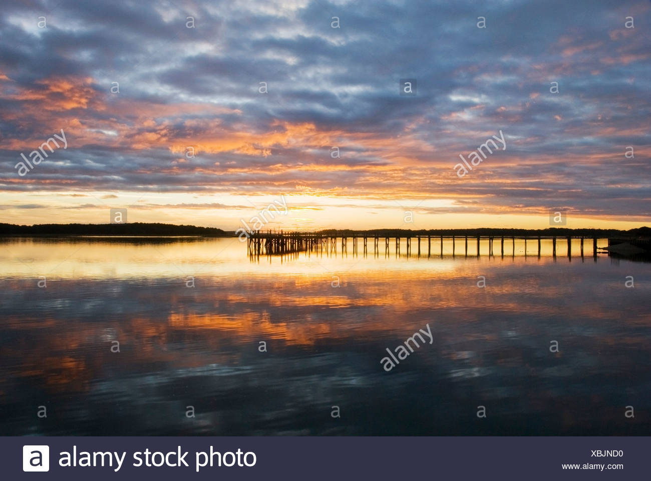 A silhouette of a pier at sunset on the Intracoastal Waterway on Hilton Head Island, SC. - Stock Image