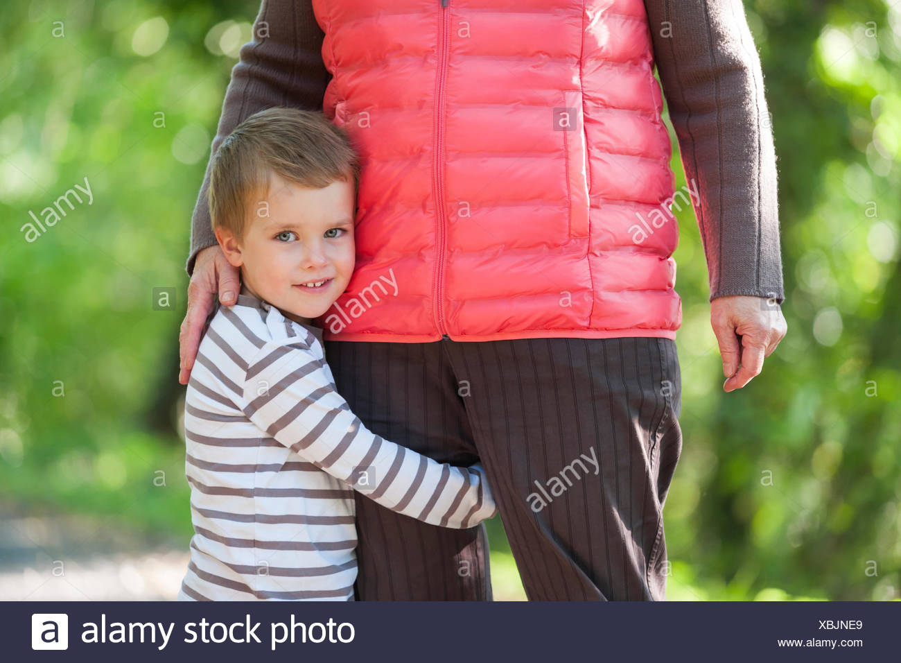 Portrait of smiling little boy embracing leg of his grandmother - Stock Image