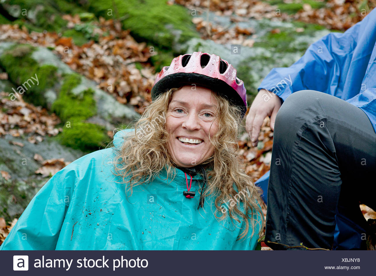 Mature woman resting from cycle ride in forest - Stock Image