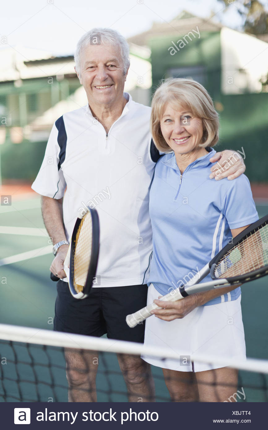 Older couple standing on tennis court - Stock Image