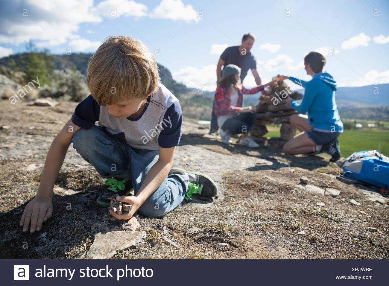 Family gathering and stacking rocks - Stock Image