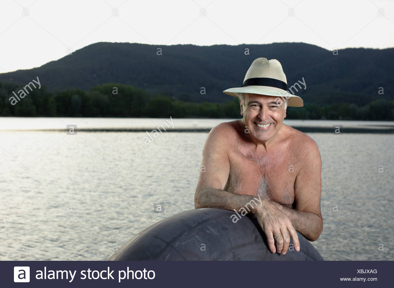 Man standing with inner tube by lake - Stock Image