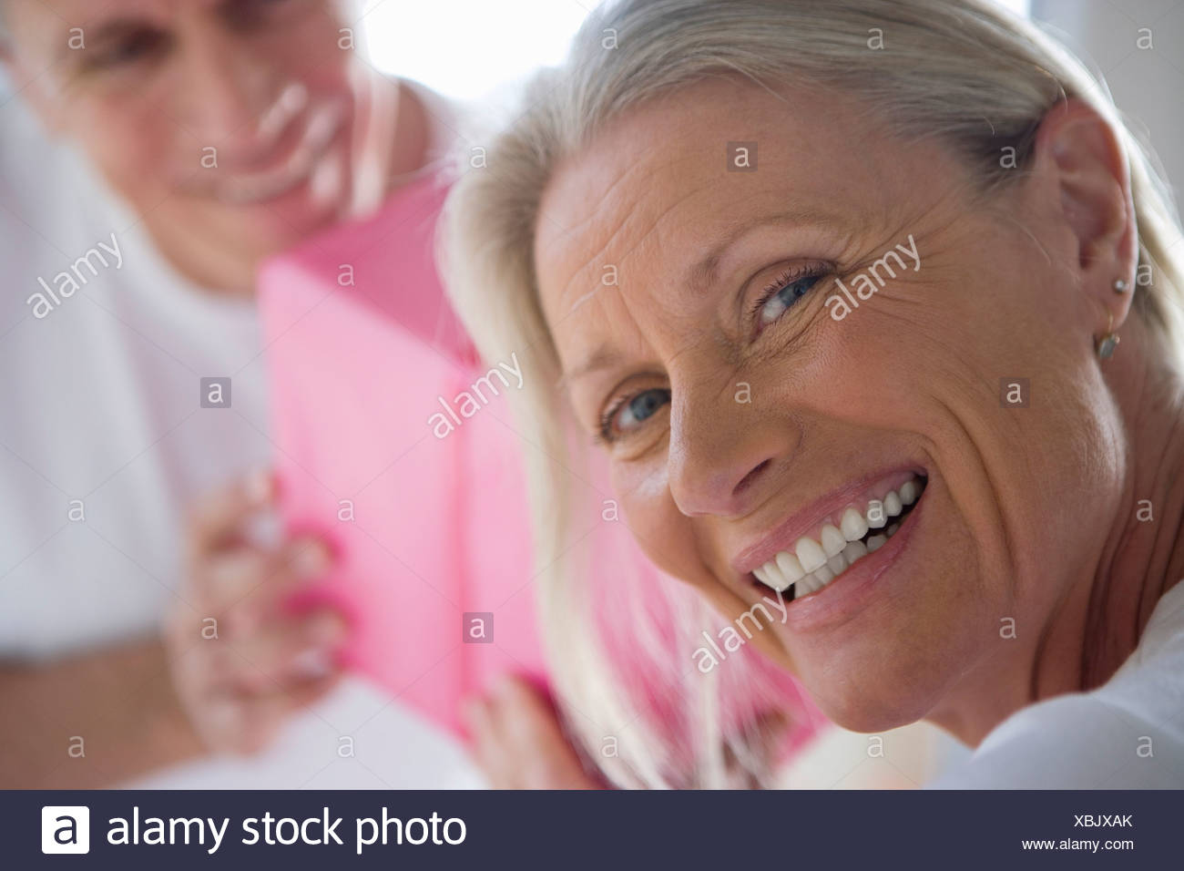 Mature man giving wife pink birthday gift, focus on woman looking over shoulder in foreground, smiling, close-up, portrait - Stock Image