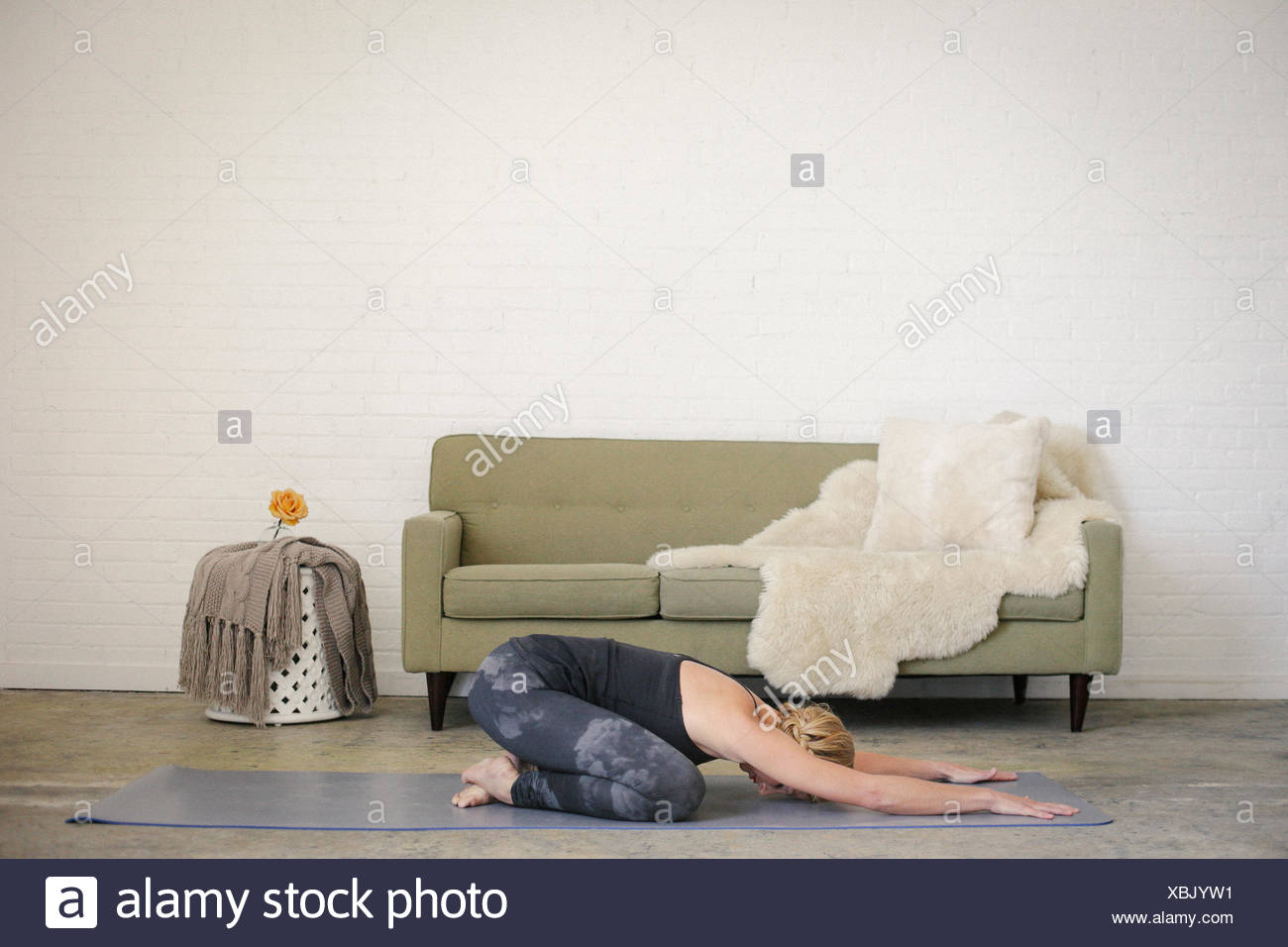 A blonde woman kneeling on a yoga mat in a room, doing yoga, her arm stretched out in front of her. - Stock Image