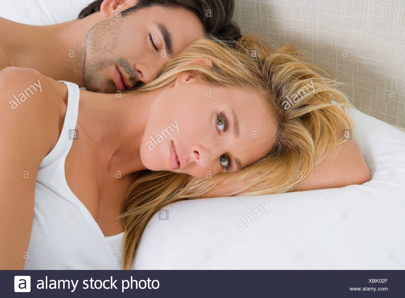 Mid adult woman and a young man lying on the bed - Stock Image