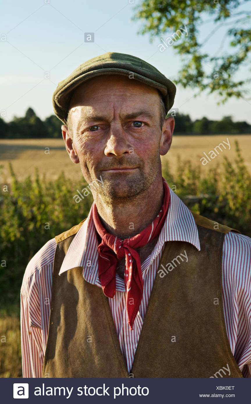 A man with a red neckerchief and flat hat, in working shirt and waistcoat. - Stock Image