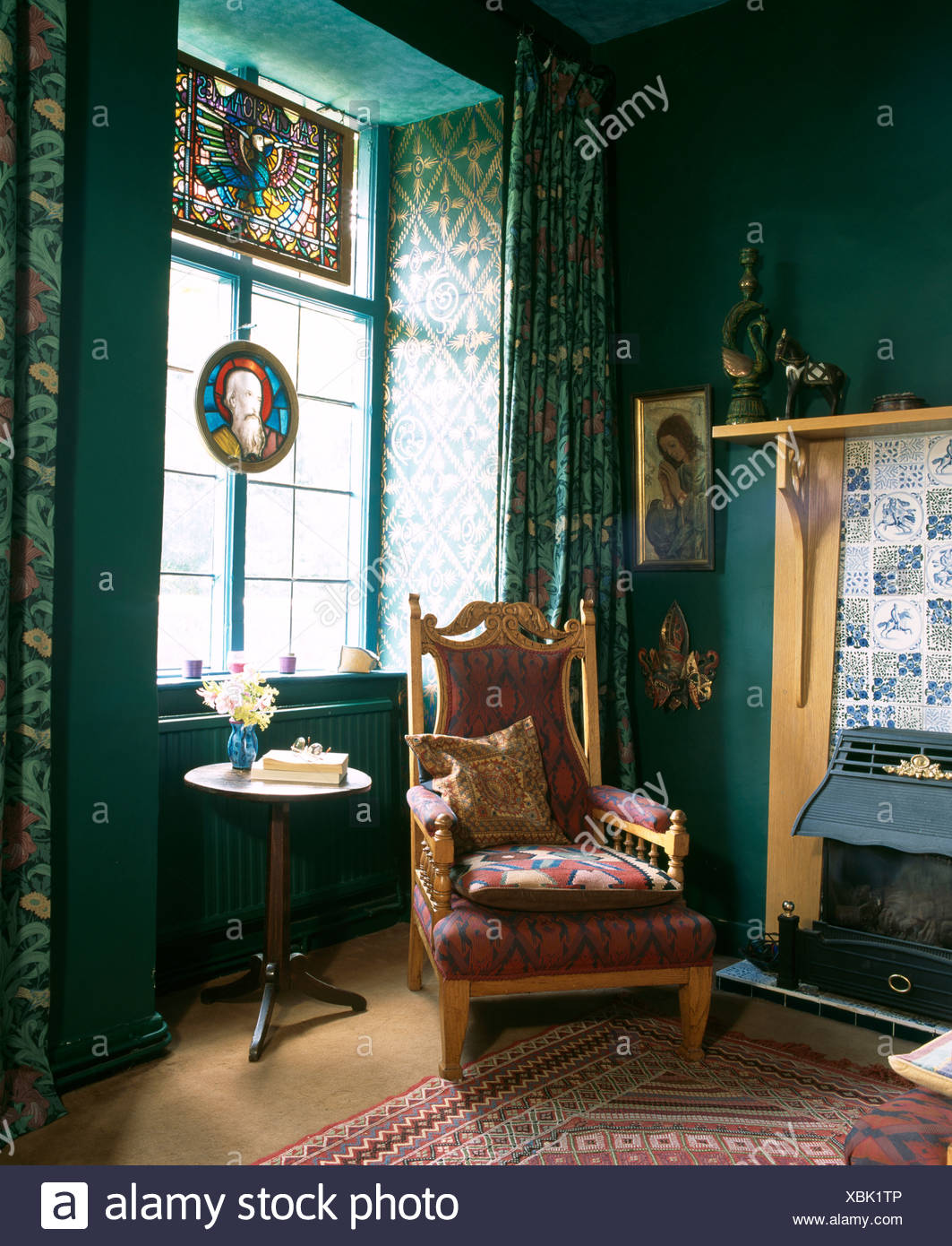 Edwardian Armchair Beside Fireplace With Electric Fire In Dark Green Living Room With Stained Glass Panel In Window Stock Photo Alamy
