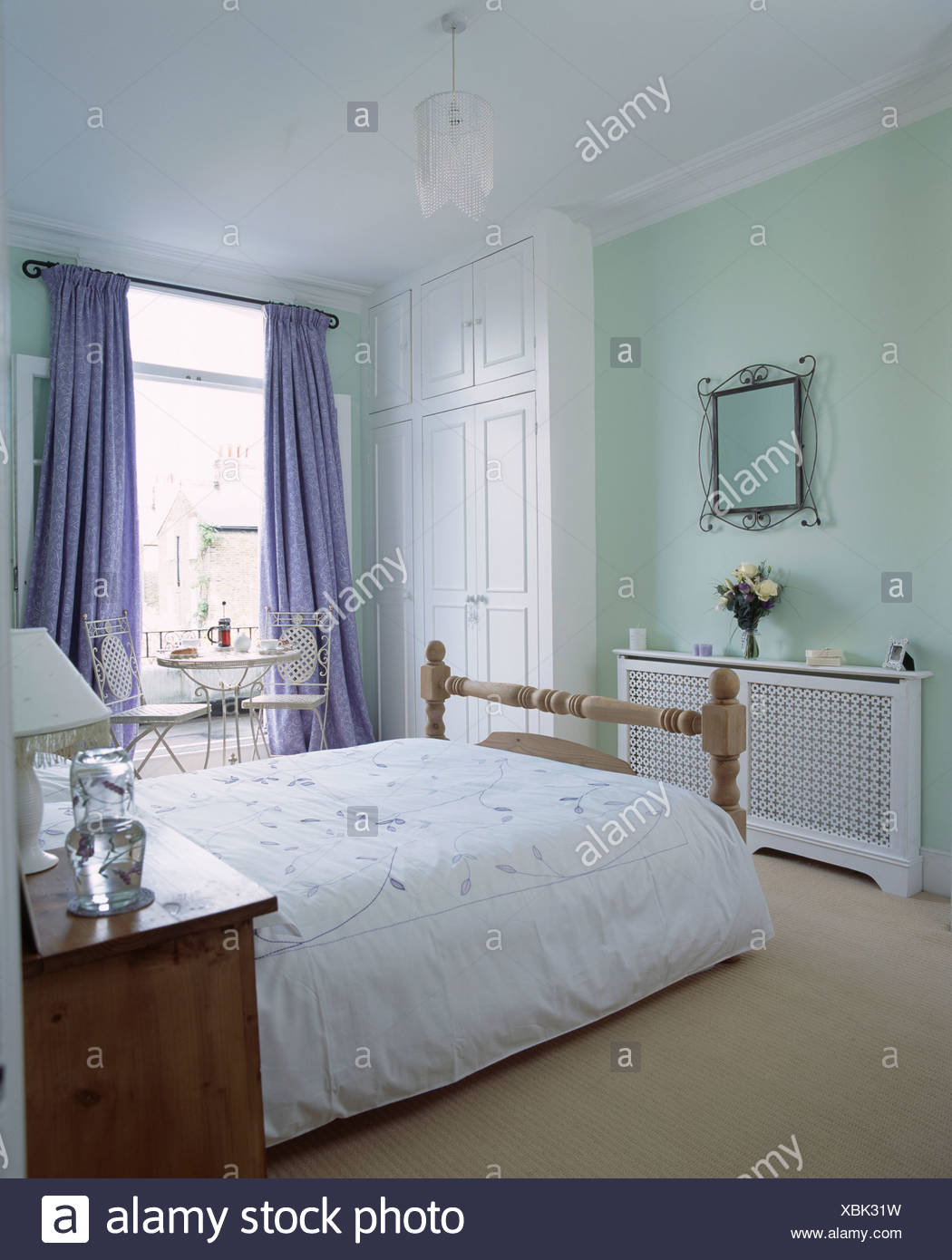 White Duvet On Bed In Pastel Green Bedroom With Fretwork Radiator Cover And Small Table And Chairs In Front Of Window Stock Photo Alamy
