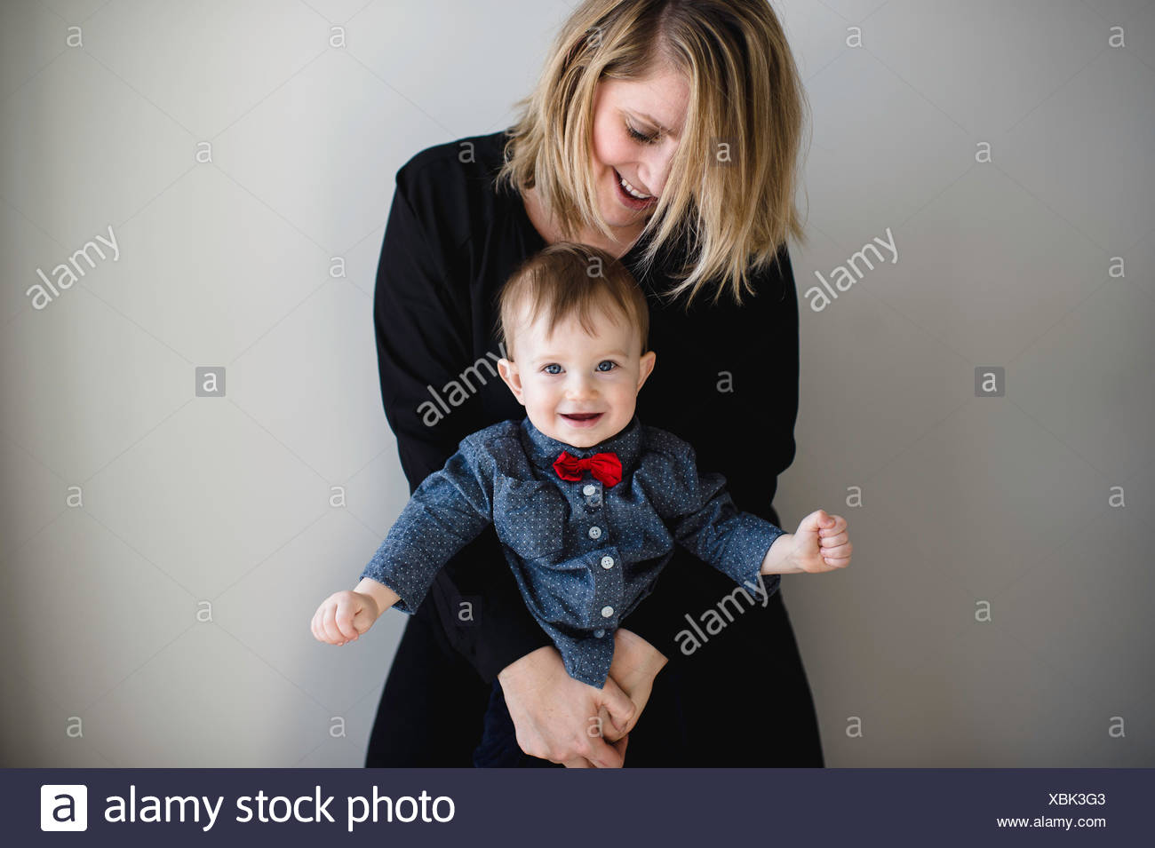 Portrait of male toddler in red bow tie being held by mother - Stock Image