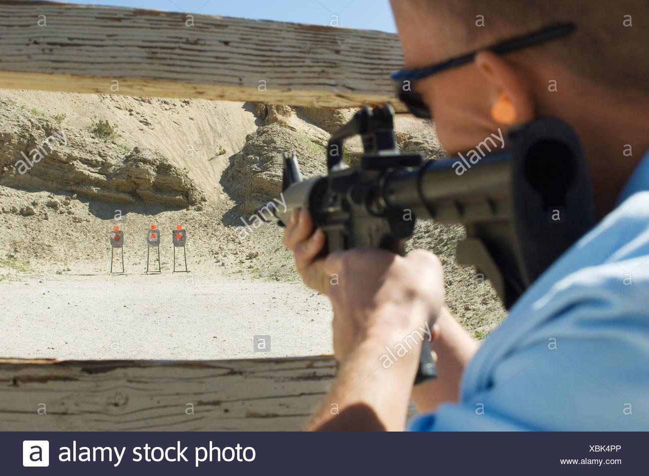 Man aiming machine gun at firing range - Stock Image