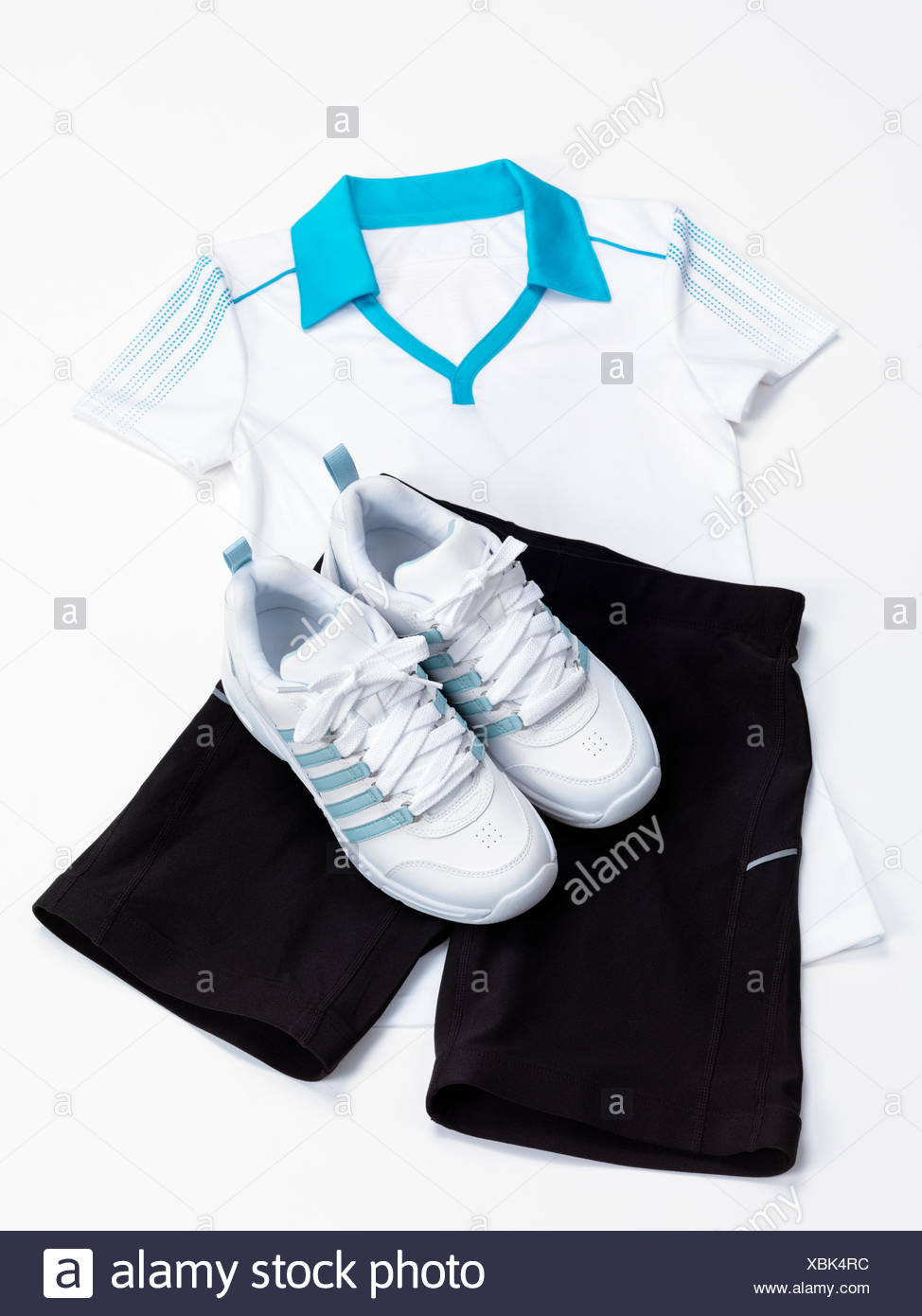 Women's sports outfit, white shirt, black fitness shorts and running shoes - Stock Image