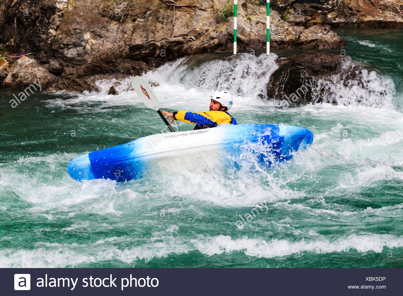 A slalom kayaker tries to stabilize his kayak while navigating the Kananaskis River at the Canoe Meadows course in Alberta. - Stock Image
