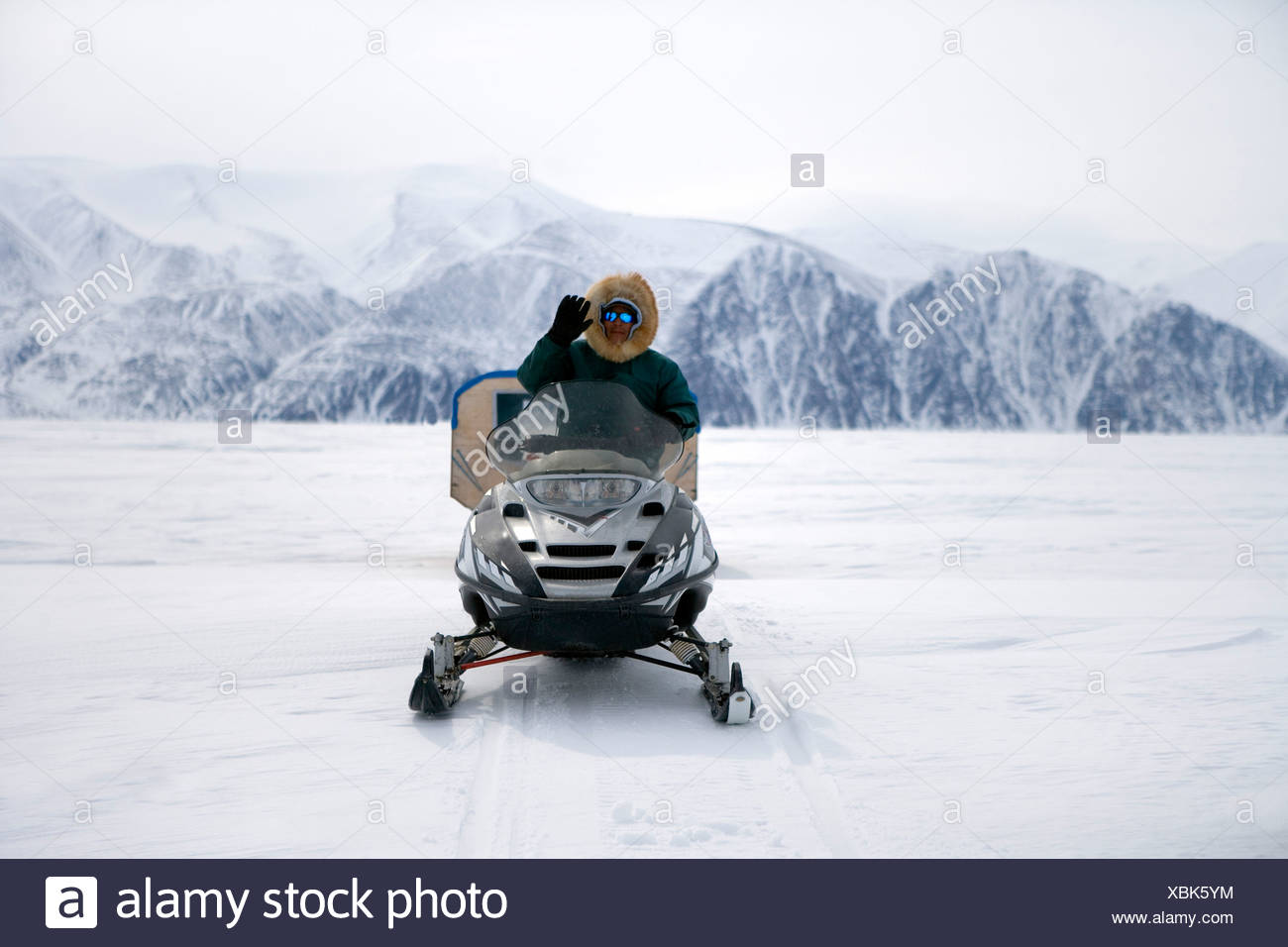 Inuit Man waving from a Skidoo, on the Ice between Baffin and Bylot Islands, Pond Inlet, Nunavut - Stock Image