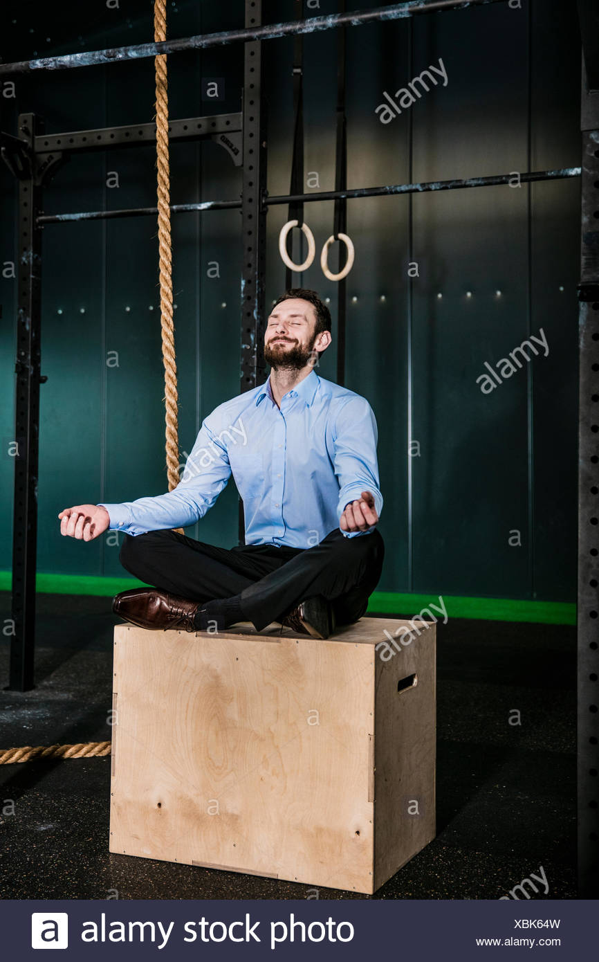 Businessman in gym siting on box, meditating - Stock Image
