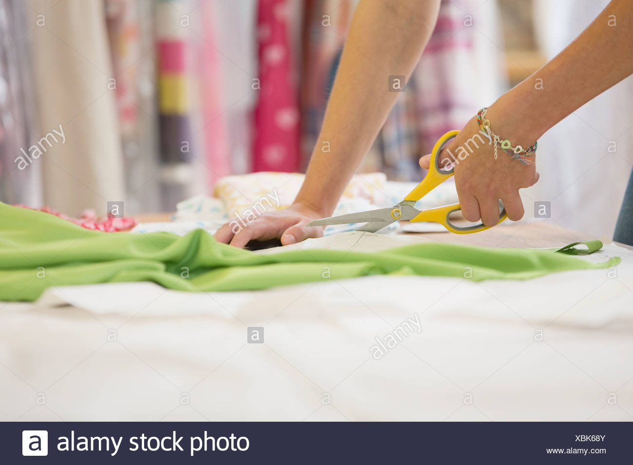 Close Up Of Fashion Designer Cutting Out Pattern From Fabric In Studio - Stock Image