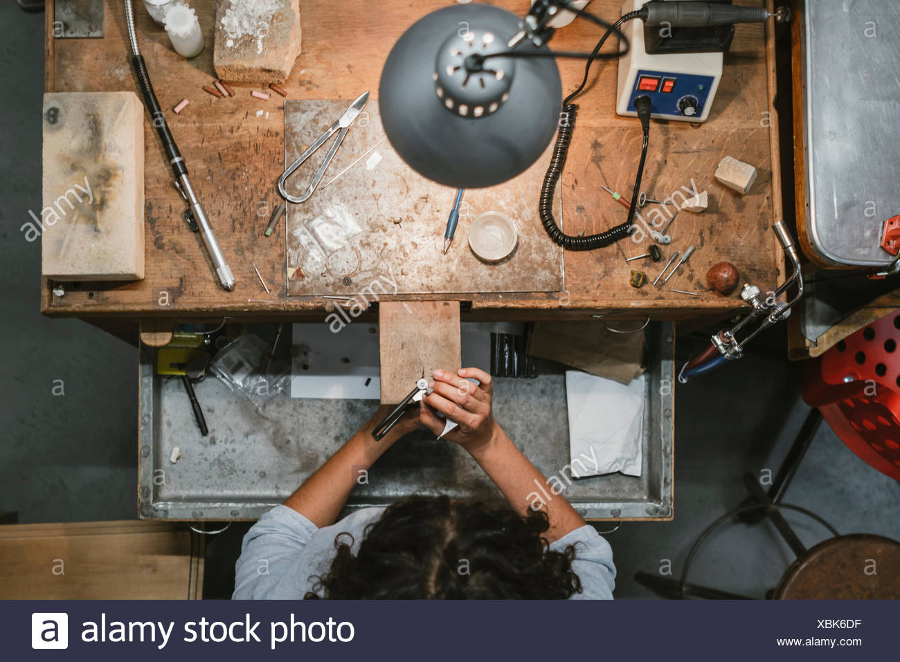 Overhead view of female jeweller using coping saw at workbench - Stock Image