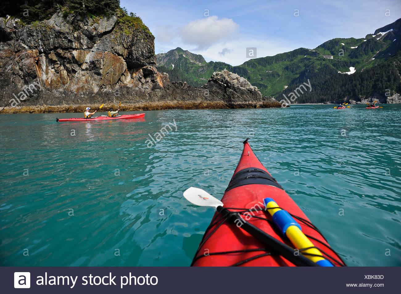 Visitors enjoy a day of kayak touring near Bulldog Cove in Kenai Fjords National Park, Alaska - Stock Image