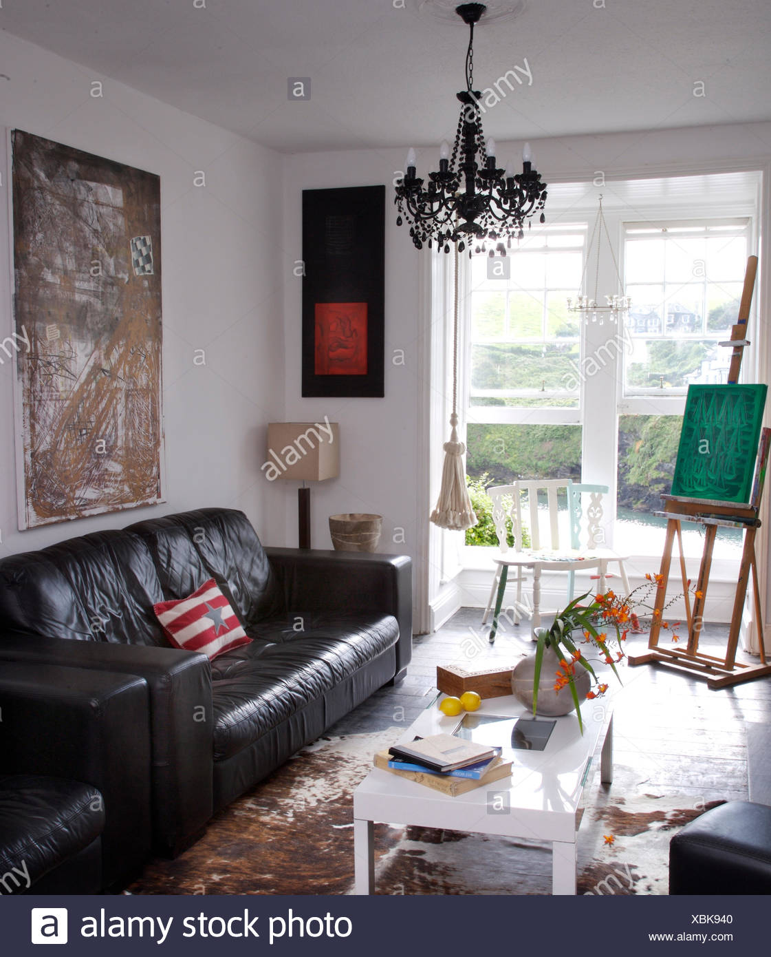 Black leather sofa in artists coastal living room with an easel