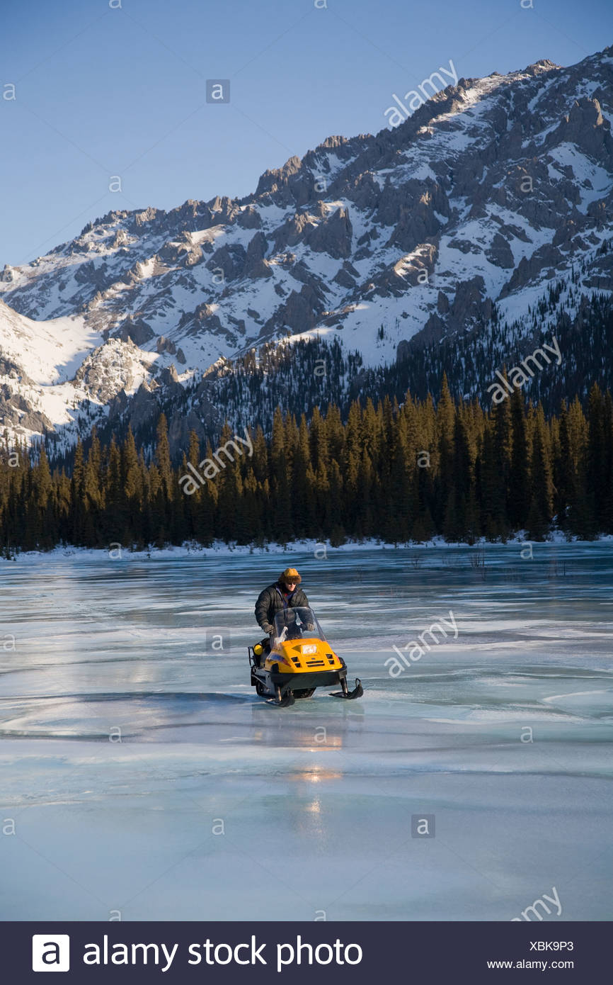 A snowmobiler negotiates overflow ice on a trail in the White Mountain National Recreation area, Interior Alaska. (MR) - Stock Image