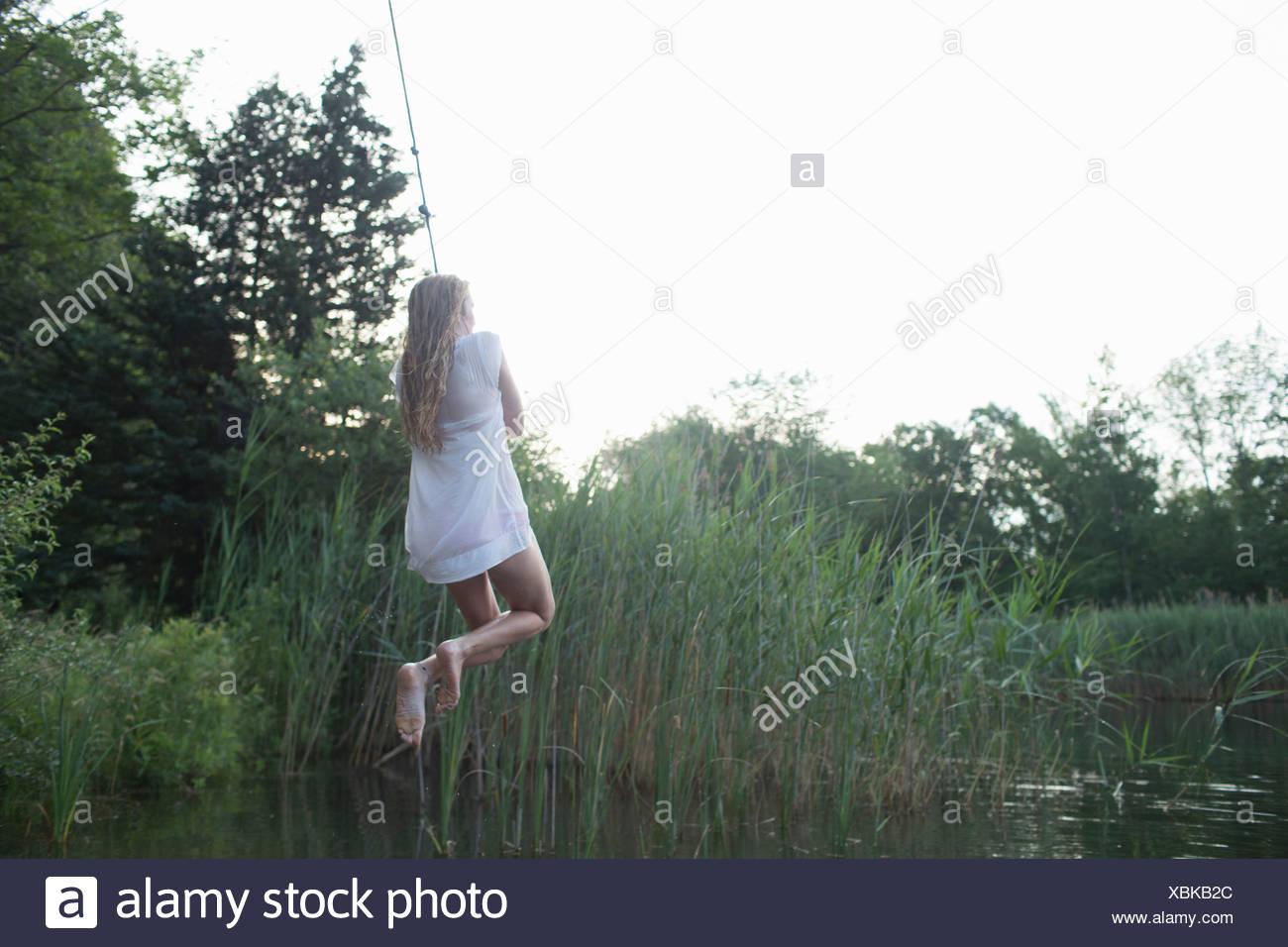 Teenage girl swinging over marshes - Stock Image