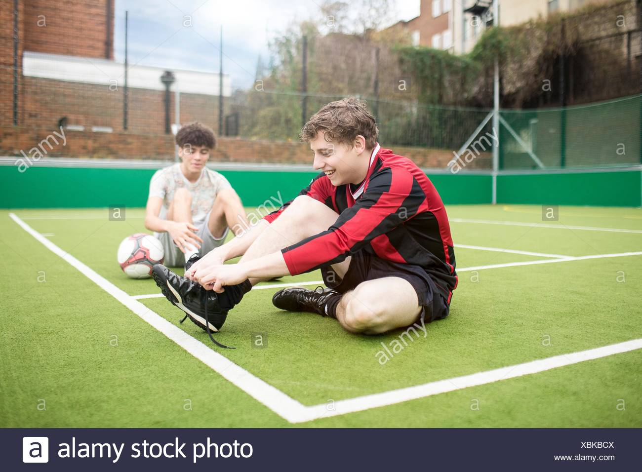 Two young men on urban football pitch, tying shoelaces - Stock Image