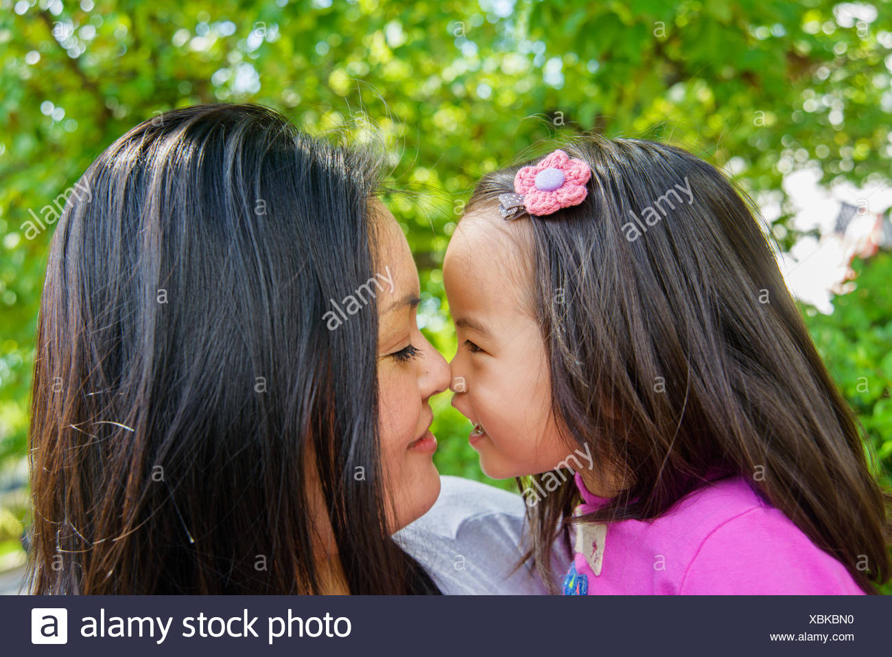 Portrait of mid adult mother and girl toddler nose to nose - Stock Image