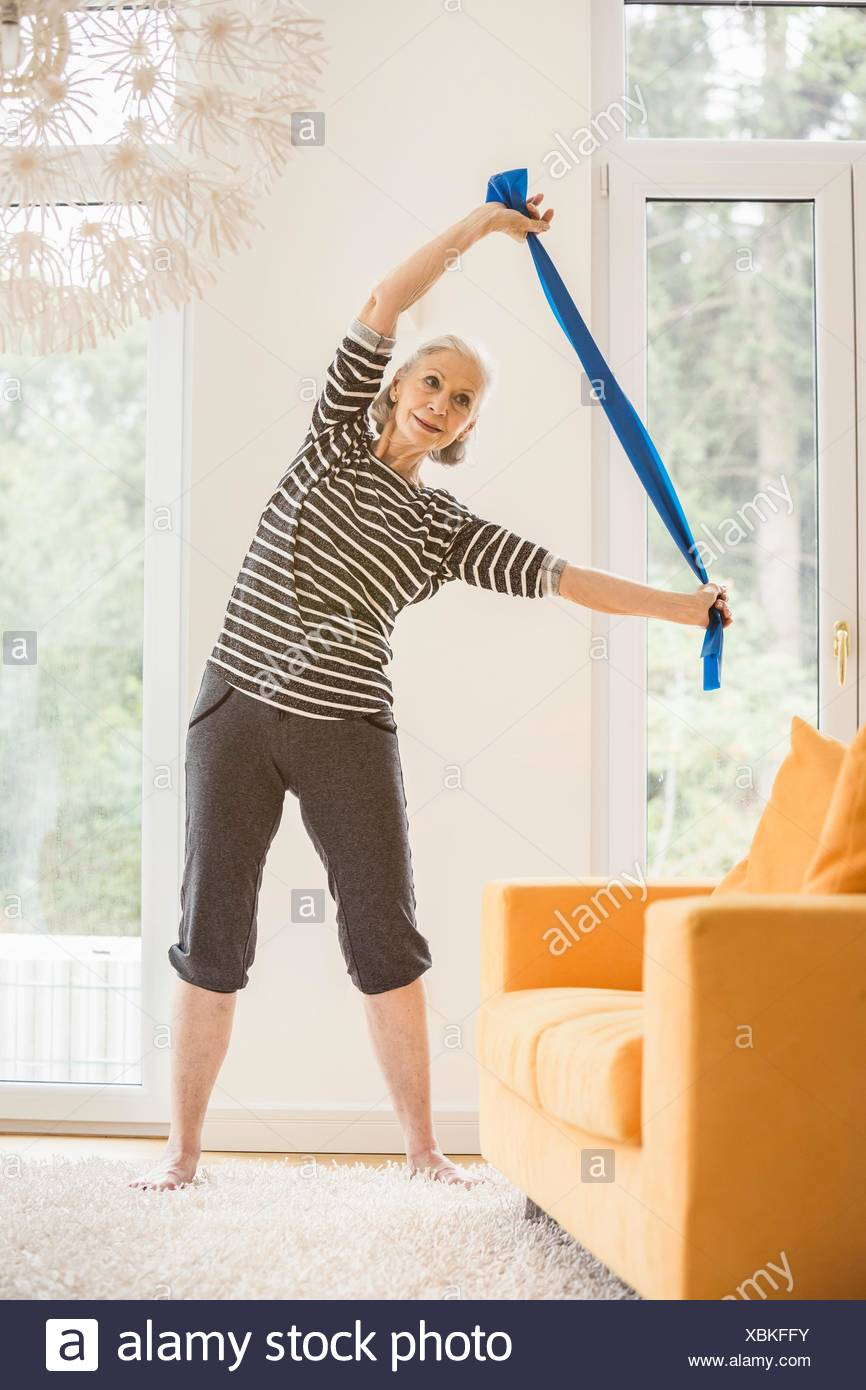 Senior woman exercising in living room using resistance band - Stock Image