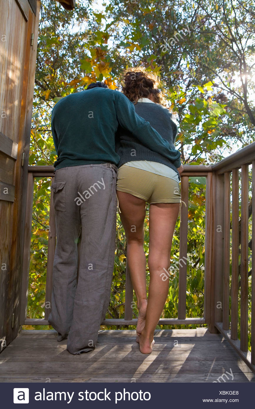 Couple outdoors on balcony being affectionate. Stock Photo