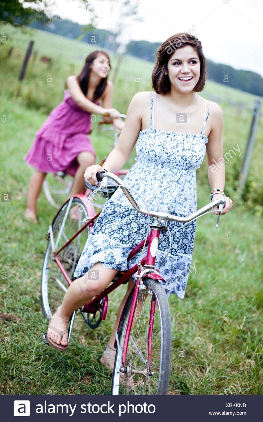 Two sisters stand with their bikes in a field. - Stock Image