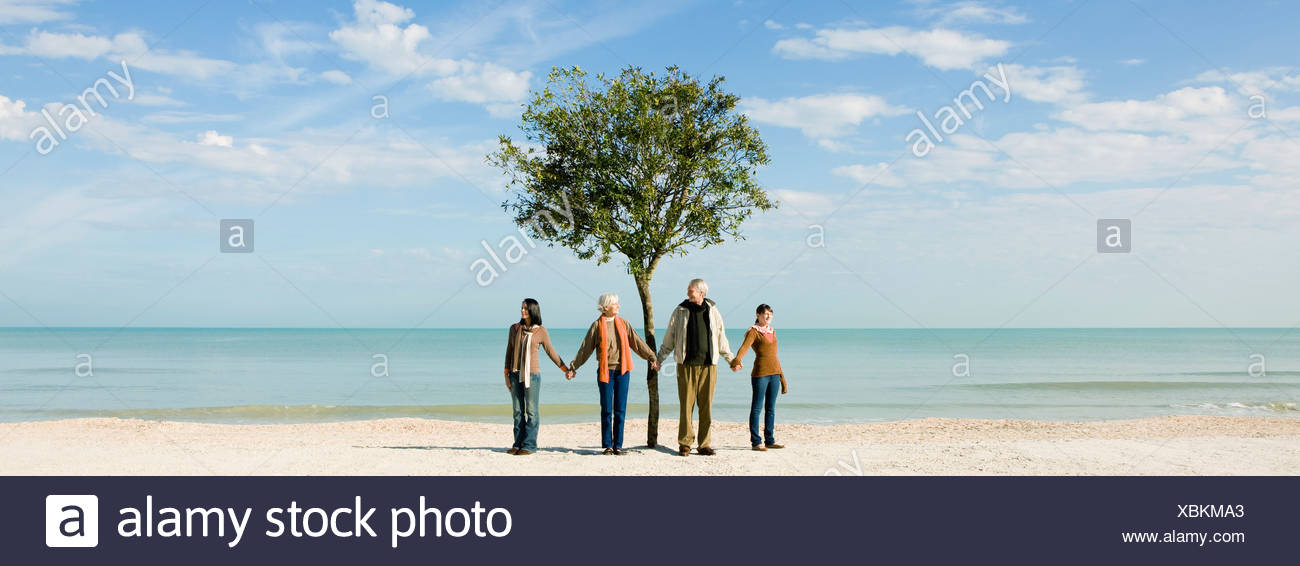Ecology concept, group of people standing in front of tree, holding hands - Stock Image