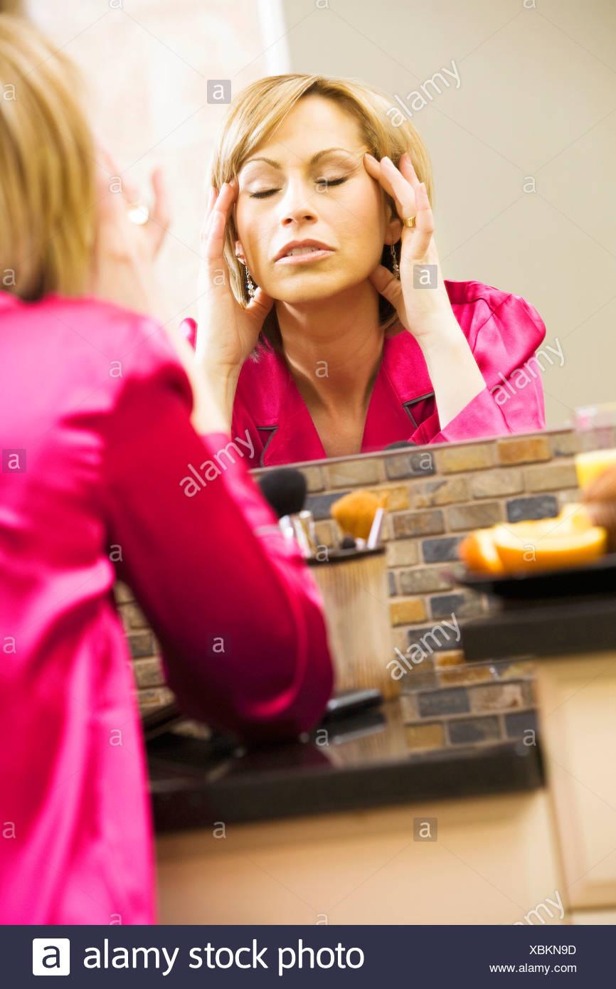 Woman massaging her head in mirror - Stock Image