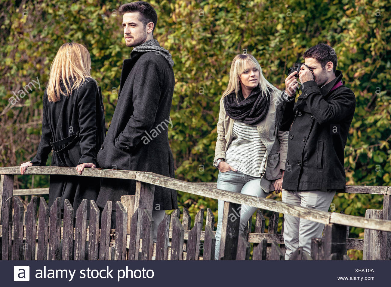 Group of friends standing on wooden bridge Stock Photo