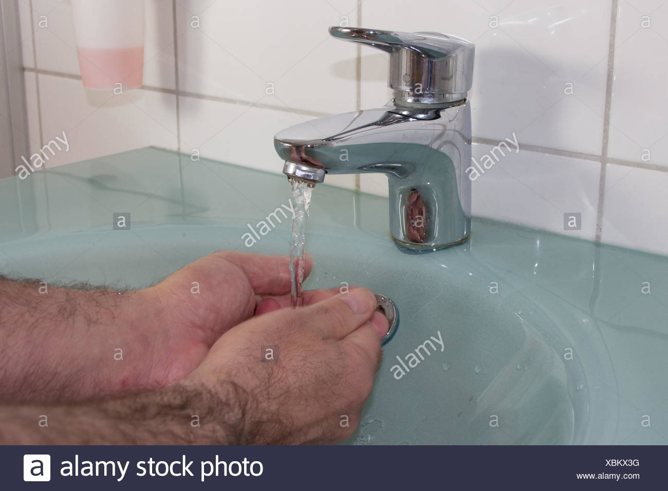 Cropped Image Of Person Washing Hands In Bathroom - Stock Image
