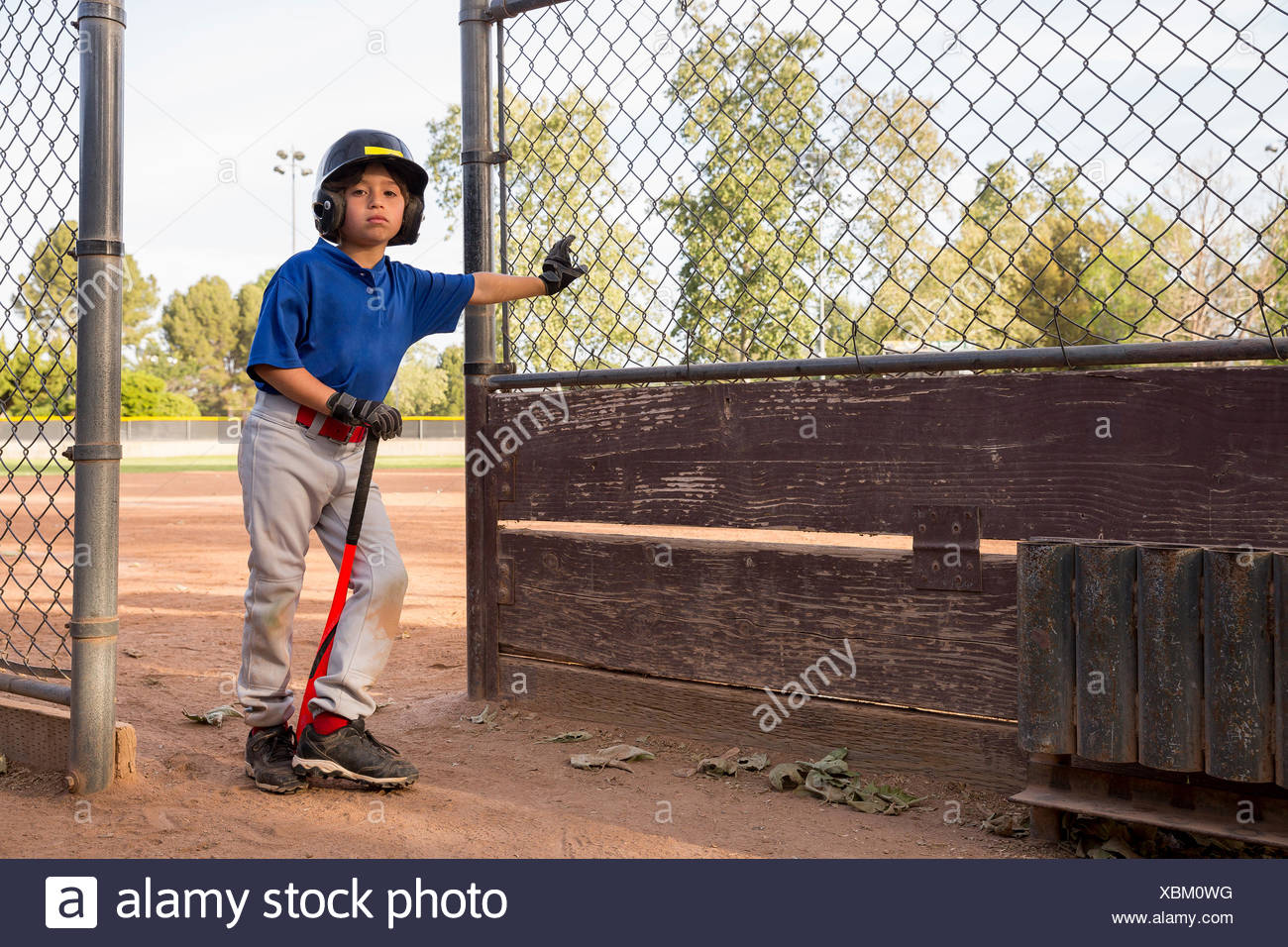 Portrait of boy with baseball bat leaning against fence at baseball practise - Stock Image