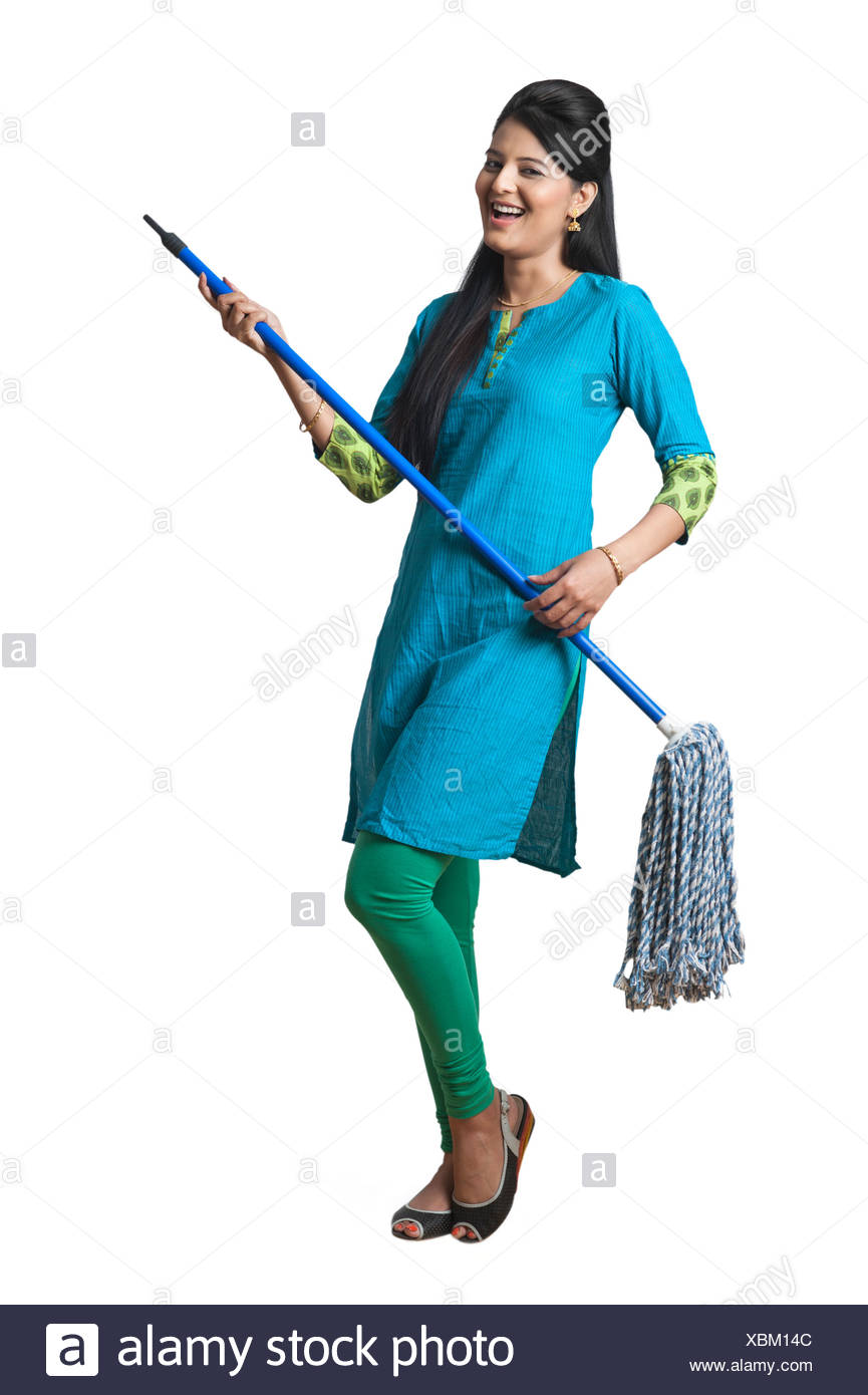 Woman holding a mop as a guitar and smiling - Stock Image