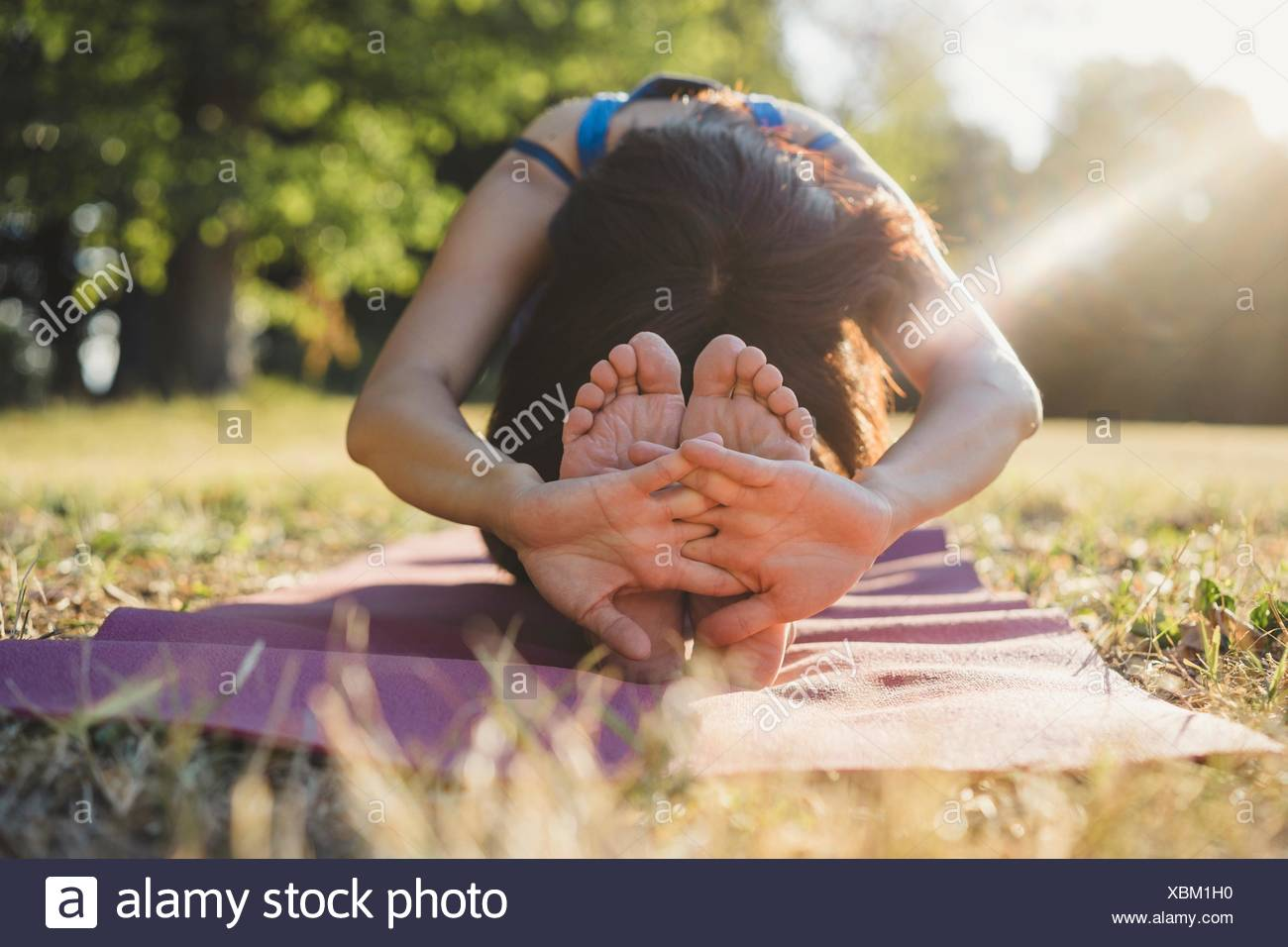 Mature woman in park, sitting, stretching, in yoga position - Stock Image