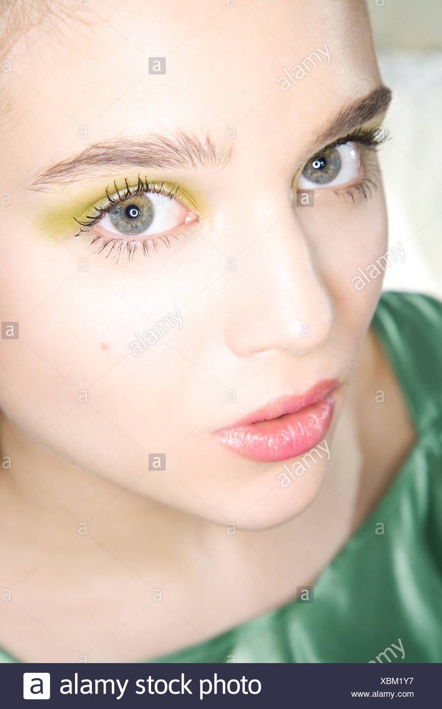 young woman with green eye shadow - Stock Image