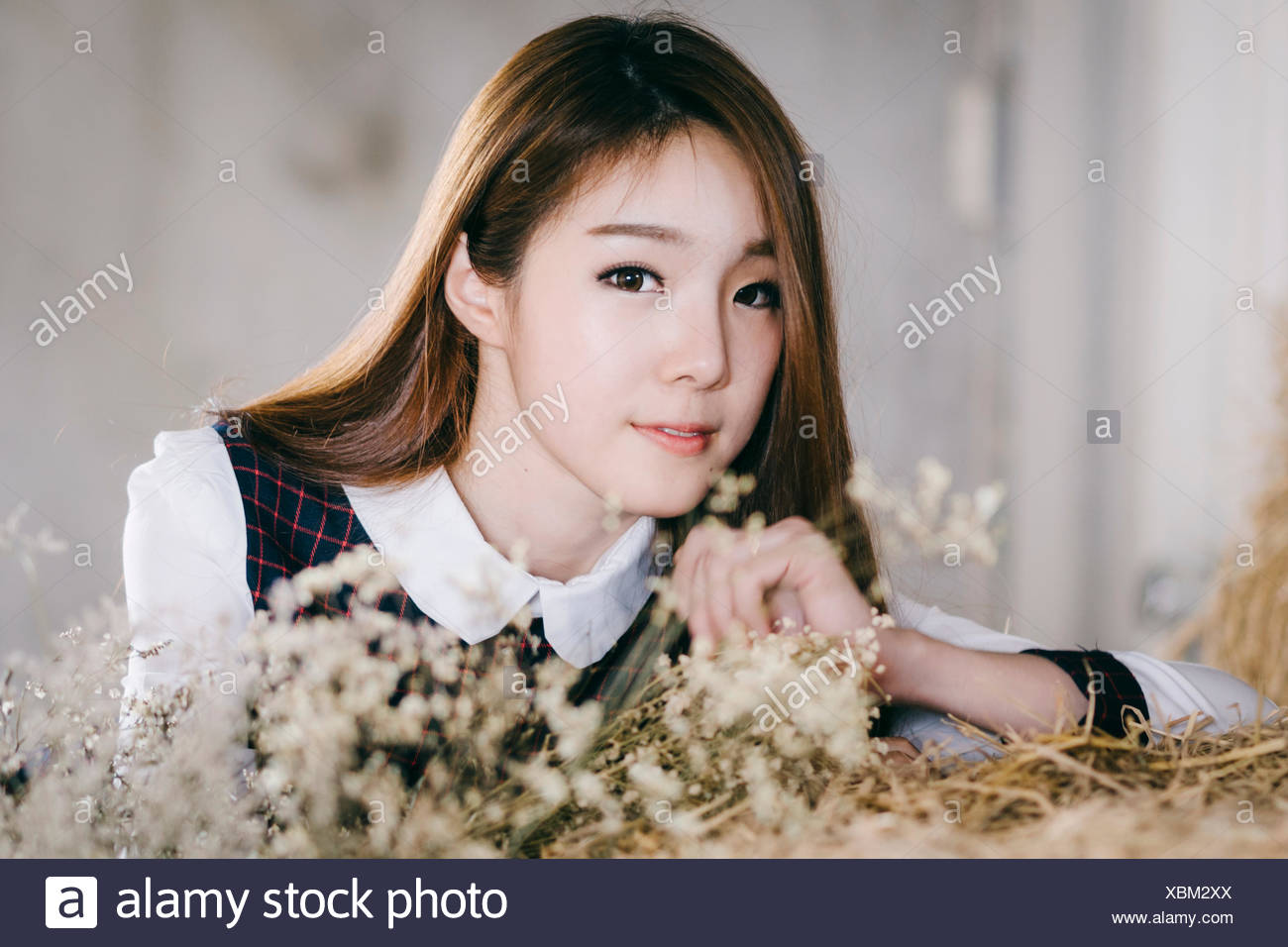 Portrait of young woman with dry flowers - Stock Image