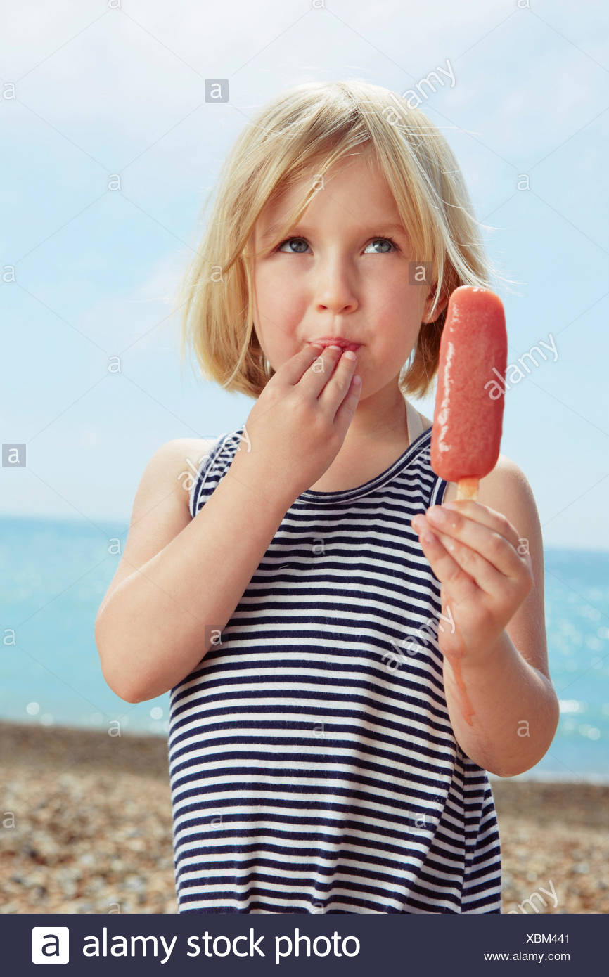 Child with fingers on lip holding ice lolly - Stock Image